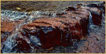 waterfall coursing amid red stones